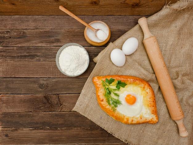 Khachapuri met eieren op zak, zout, bloem en eieren. houten tafel, kopie ruimte Premium Foto