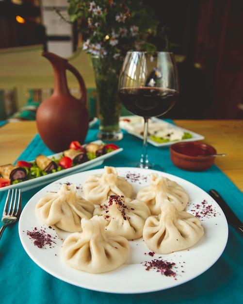 Khinkali geserveerd met aubergine broodjes en een glas wijn Gratis Foto
