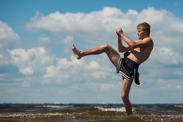 Kickboxer trapt in de open lucht in de zomer tegen de zee. Premium Foto