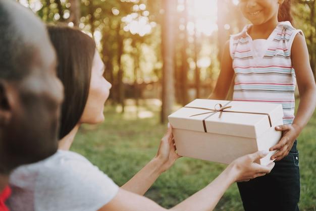 Kid geeft aanwezig in vak aan ouders op picknick. Premium Foto