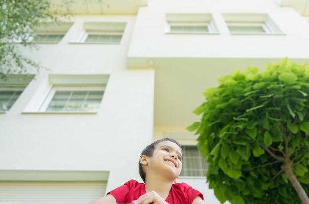 Kid in de achtertuin van mooi modern huis Premium Foto