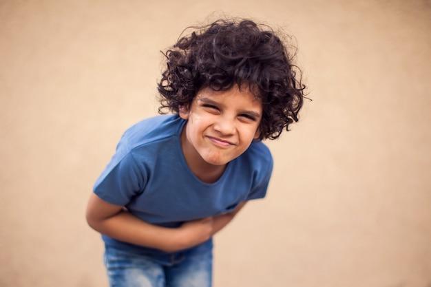 Kid jongen voelt sterke buikpijn. kinderen, gezondheidszorg en geneeskunde concept Premium Foto