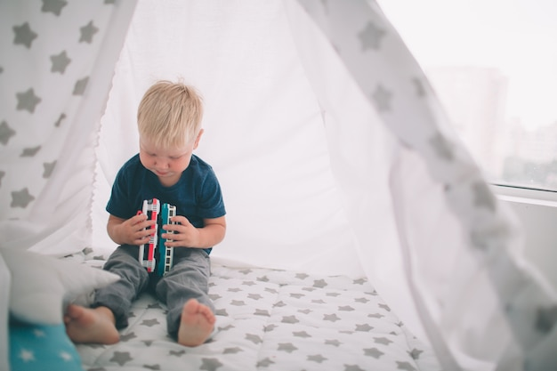 Kid ligt op de vloer. de jongen speelt thuis in de ochtend in speelgoedauto's. casual levensstijl in de slaapkamer. Premium Foto