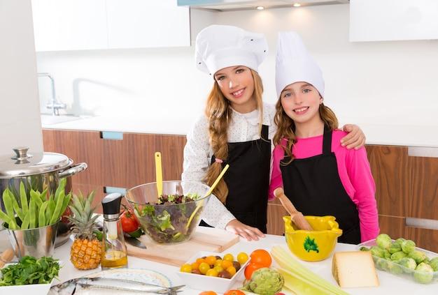 Kid meisjes junior chef-kok vrienden knuffel samen op kookschool Premium Foto