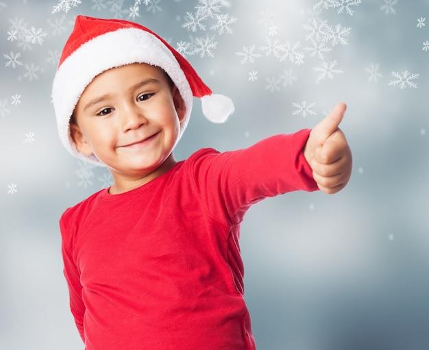 Kid met duim omhoog en sneeuw achtergrond Gratis Foto