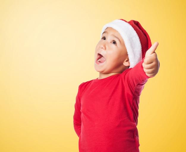 Kid met santa's hoed en duim omhoog Gratis Foto