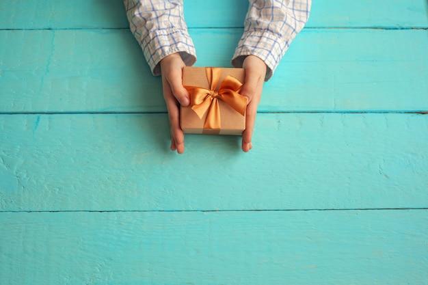 Kid's handen houden geschenkdoos verpakt in ambachtelijk papier en vastgebonden met strik. Premium Foto