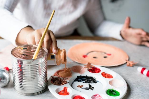 Kid santa schilderij op een papieren bord Gratis Foto