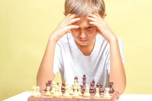 Kid schaken. jongen die schaakbord bekijkt en over zijn strategie denkt. Premium Foto
