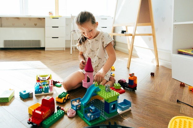 Kid spelen met kleurrijke blokken. meisje de bouwtoren van blokspeelgoed. educatief en creatief speelgoed en spelletjes voor jonge kinderen. speeltijd en rommel thuis Premium Foto