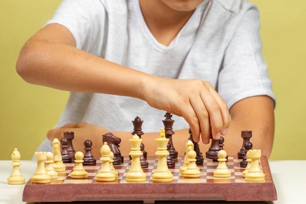 Kid zitten in de buurt van schaakbord en schaakspel spelen Premium Foto