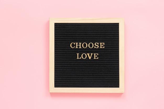 Kies liefde. motiverende citaat in gouden letters op zwart letterbord op roze achtergrond Premium Foto