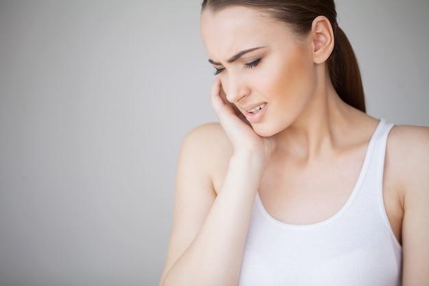 Kiespijn. vrouw gevoel tandpijn. close-up van mooi droevig meisje die aan sterke tandpijn lijden. aantrekkelijke vrouw gevoel pijnlijke kiespijn. tandgezondheid en zorgconcept Premium Foto