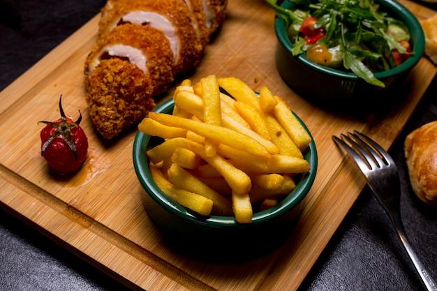 Kiev stijl kotelet op de houten plank met frietjes arugula tomaat komkommer saus zijaanzicht Gratis Foto