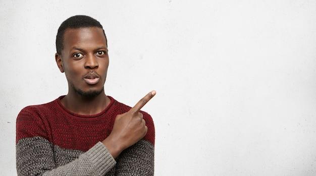 Kijk hier eens naar. verbijsterd en opgewonden jonge afro-amerikaanse man gekleed terloops wijzend zijn wijsvinger omhoog op lege grijze muur met copyspace Gratis Foto