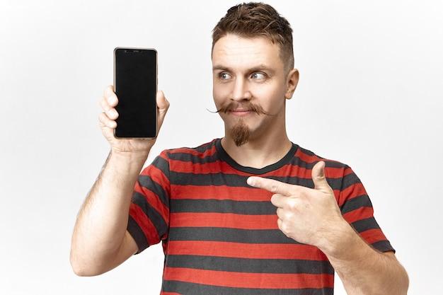 Kijk hiernaar. knappe emotionele jonge verkoper met stijlvolle baard en snor poseren in studio met slimme telefoon in zijn hand, wijsvinger wijzend op het lege copyspace-scherm, gadget presenteren Gratis Foto