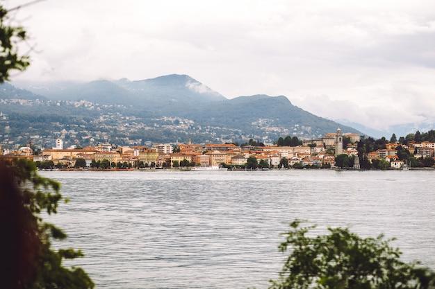 Kijk van veraf naar het meer voor de bergen bedekt met mist Gratis Foto