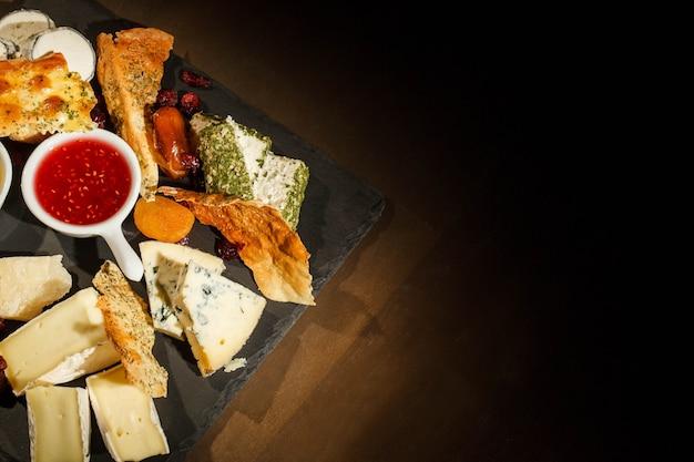 Kijk vanaf boven bij zwarte schotel met blauwe kaas, camembert, brie Gratis Foto
