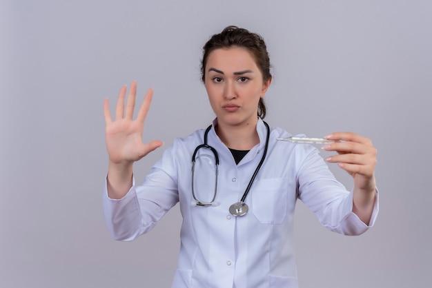 Kijkend naar camera jonge arts medische jurk dragen stethoscoop houden thermometer en toont stop gebaar op witte muur Gratis Foto