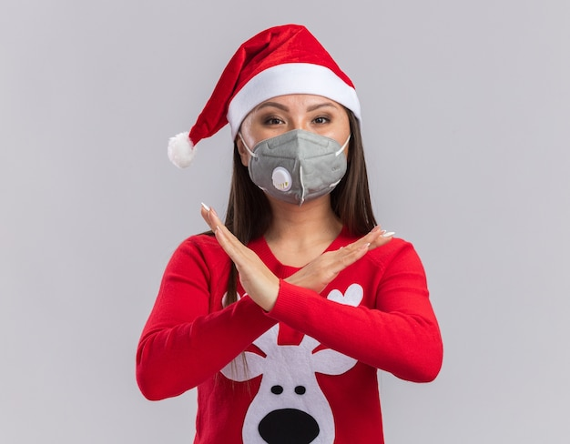 Kijkend naar de camera jong aziatisch meisje met kerstmuts met trui en medische masker met gebaar van nee geïsoleerd op een witte achtergrond Gratis Foto
