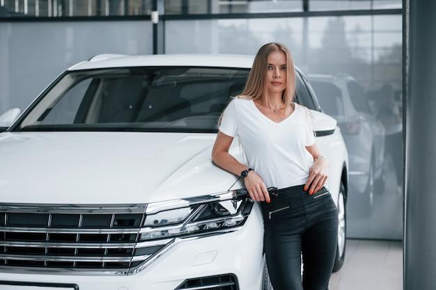 Kijkend naar de camera. meisje en moderne auto in de salon. overdag binnenshuis. een nieuw voertuig kopen Gratis Foto
