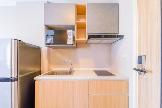 Kijkend naar een kleine lege keuken met fornuis, koelkast en kasten Premium Foto