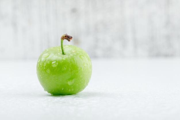 Kille groene pruim op grungy en witte muur. zijaanzicht. Gratis Foto