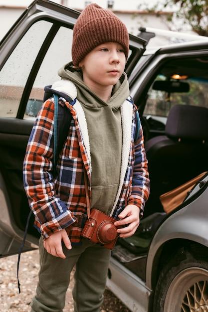 Kind buiten met auto op een roadtrip Gratis Foto
