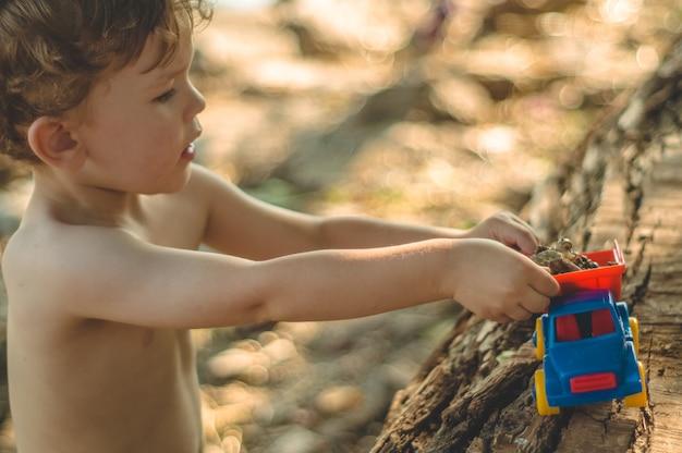 Kind buiten spelen. kid we gieten het zand in de rode vrachtwagen. kinderen straatspellen. een jongen die met een machine op het grote blok speelt Premium Foto