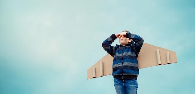 Kind buiten spelen papier vleugels Premium Foto