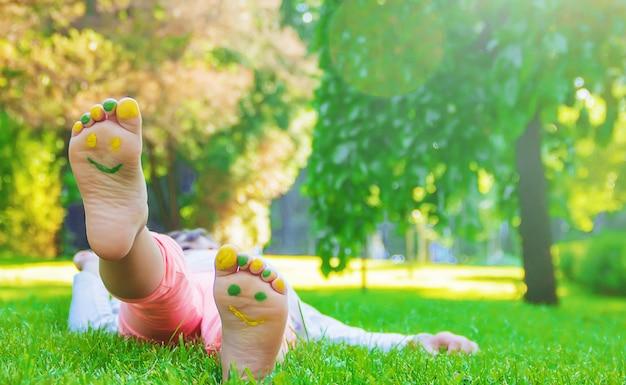 Kind dat op groen gras ligt. kind plezier buitenshuis in het voorjaar van park. Premium Foto