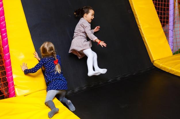 Kind dat op kleurrijke speelplaatstrampoline springt. kinderen springen in opblaasbaar kasteelfeestje Premium Foto