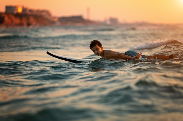 Kind dat op tropisch strand surft Premium Foto