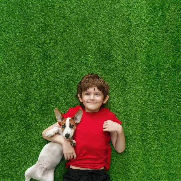 Kind dat puppyhefboom russell omhelst en op groen tapijt ligt. Premium Foto