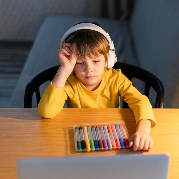 Kind dat virtuele cursussen volgt en kleurrijke markeringen heeft Gratis Foto