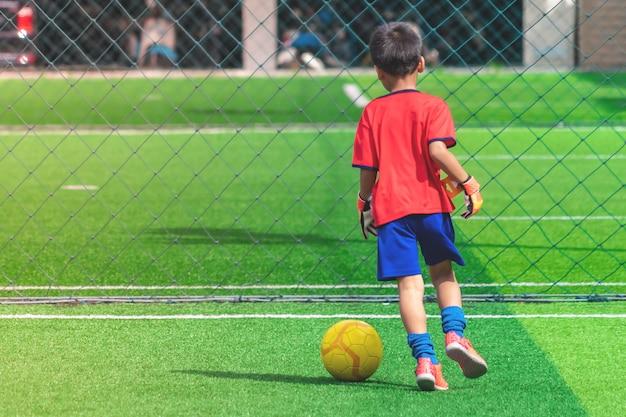 Kind dribbelt voetbal op een veld Premium Foto