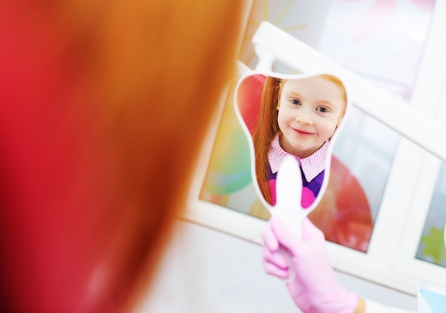 Kind-een klein roodharig meisje glimlachen die in de spiegelzitting kijken als tandvoorzitter. Premium Foto
