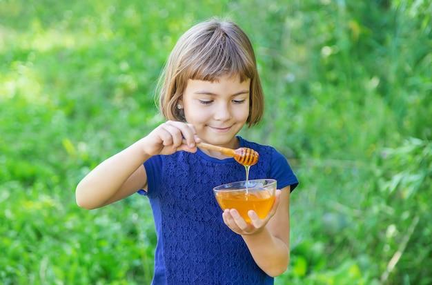 Kind een plaat met honing in handen Premium Foto