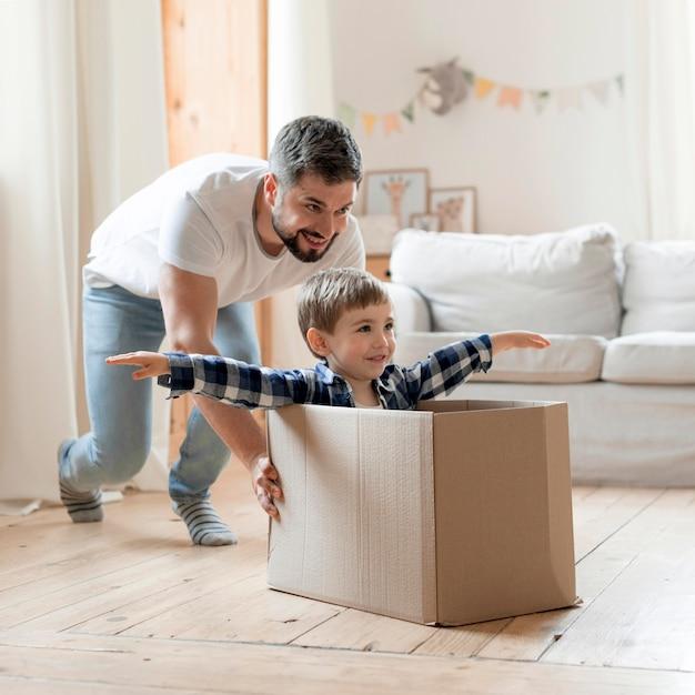 Kind en vader spelen met een doos in de woonkamer Gratis Foto