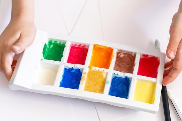 Kind handen met verf palet Premium Foto