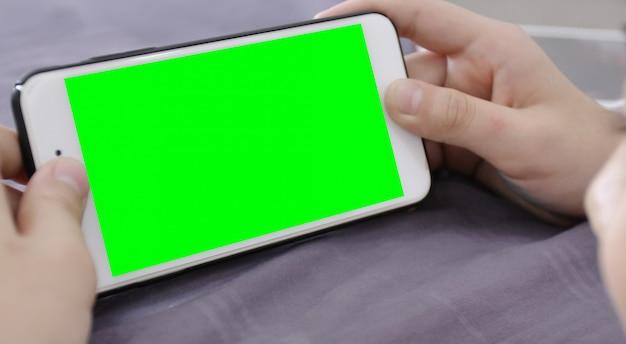 Kind houdt een telefoon in zijn hand met een groen scherm. Premium Foto