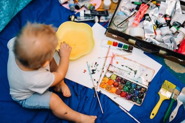 Kind in de buurt van borstels, aquarel kleuren en vak zittend op de coverlet Gratis Foto