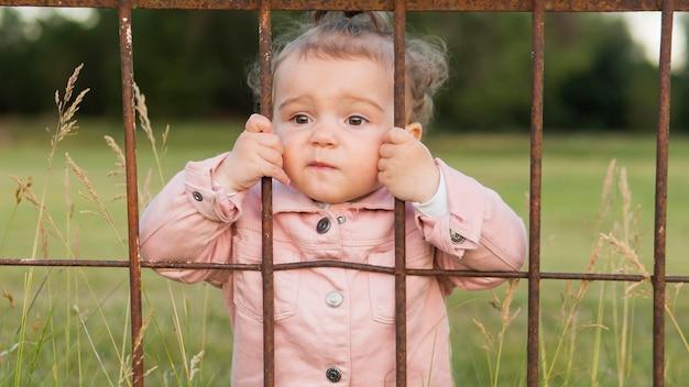 Kind in roze kleren achter het middelgrote schot van parkbars Gratis Foto