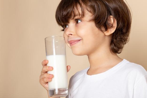 Kind jongen zoete witte volle melk drinken op roze Gratis Foto