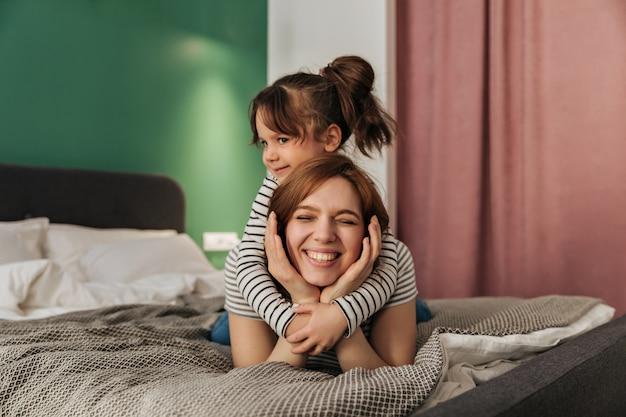 Kind knuffelt moeder. vrouw en haar dochter liggen op bed. Gratis Foto