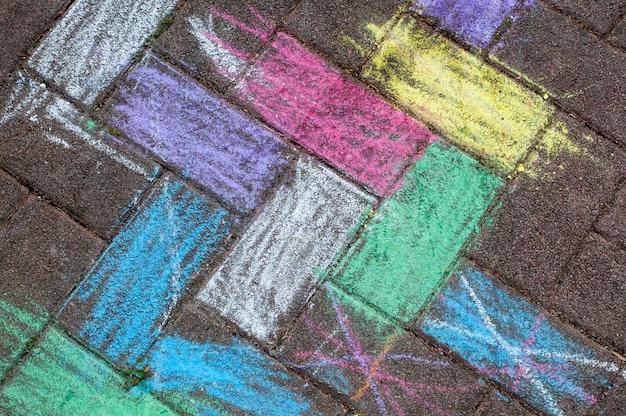 Kind krijt foto op de stoep. multi-coloured krijt die van kinderen op het asfalt trekken. achtergrond, bovenaanzicht, van bovenaf. Premium Foto