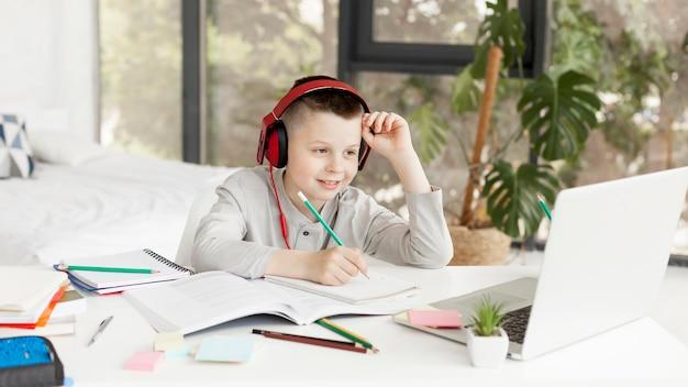 Kind leert cursussen online en draagt een koptelefoon Gratis Foto