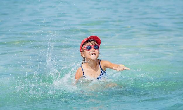 Kind maakt spray op de zee Premium Foto