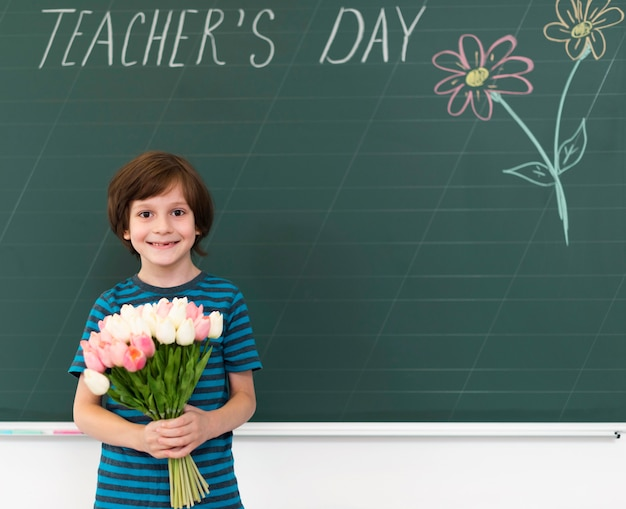 Kind met een boeket bloemen naast een schoolbord Gratis Foto