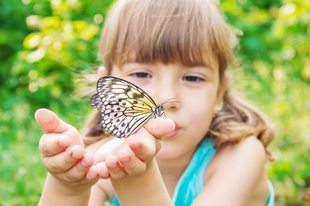 Kind met een vlinder. idee leuconoe. selectieve aandacht. Premium Foto